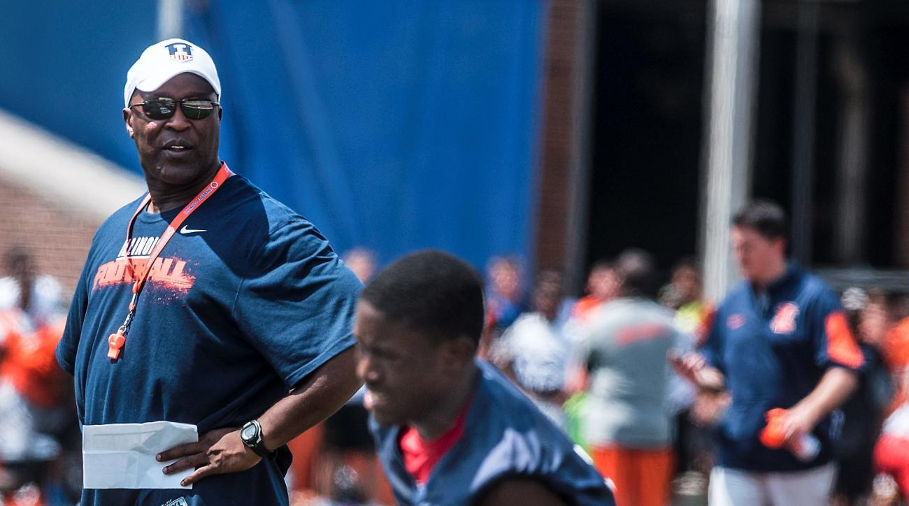 In this June 12, 2016 photo, University of Illinois head football coach Lovie Smith, left, watches a football camp for high school athletes at Memorial Stadium in Champaign, Ill. When he got to campus back in March, coach Smith counted 50 or 60 Illini pla