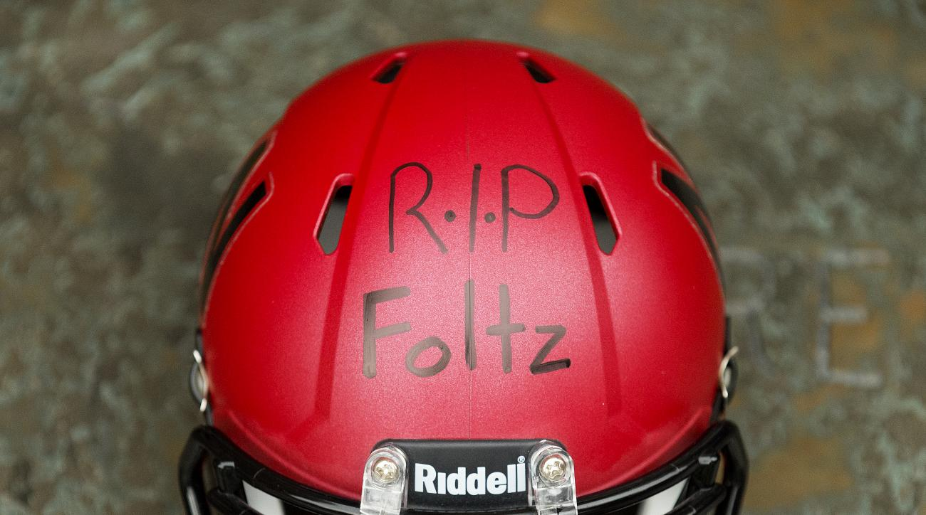 "A Nebraska mini-football helmet inscribed ""RIP Foltz,"" for Nebraska punter Sam Foltz is seen during a vigil for Foltz, Sunday, July 24, 2016, in Lincoln, Neb. Foltz and former Michigan State punter Mike Sadler died in a car crash in Wisconsin after workin"