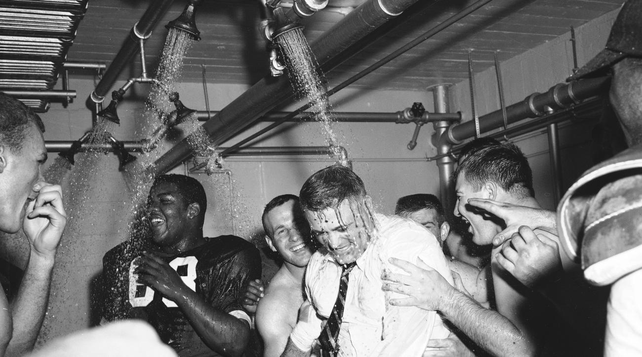 FILE - In this Nov. 16, 1957, file photo, Ohio State football coach Woody Hayes, center, gets a clothes-on dunking in the Ohio State dressing room shortly after Ohio State University won the Big Ten championship and clinched a Rose Bowl bid by defeating I