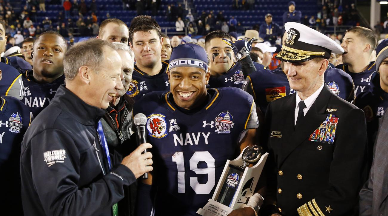 FILE - This Dec. 28, 2015,  file photo shows Navy quarterback Keenan Reynolds (19) holding a trophy after being named Most Valuable Player after the Military Bowl NCAA college football game against Pittsburgh in Annapolis, Md. To no ones surprise, the ver