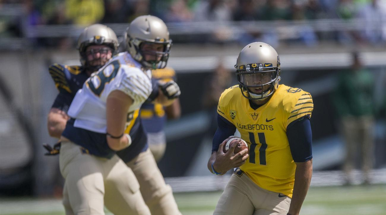 FILE - In this April 30, 2016, file photo, Oregon quarterback Travis Jonsen scrambles with the football during the Oregon Spring Game in Eugene, Ore. Oregon coach Mark Helfrich says he hopes to have a decision on the starting quarterback about 10 days bef
