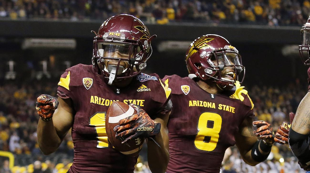 FILE - In this Jan. 2, 2016, file photo, Arizona State receiver Tim White, left, celebrates with teammate Lloyd Carrington after scoring two points after returning a blocked extra-point kick against West Virginia during the first half of the Cactus Bowl N