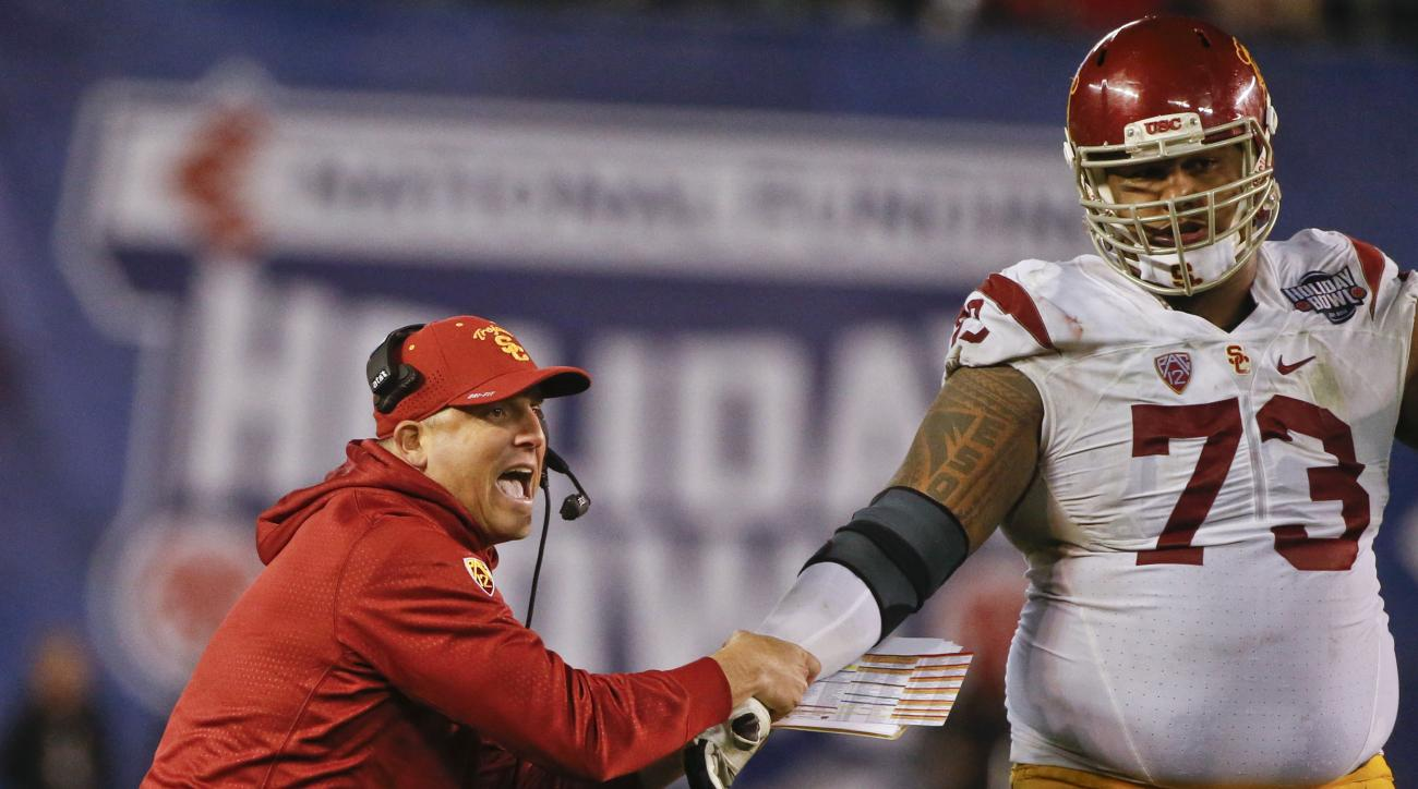 FILE - In the Dec. 30, 2015, file photo, Southern California head coach Clay Helton, left, pulls on the arm of offensive tackle Zach Banner during the last minutes of the Holiday Bowl NCAA college football game against Wisconsin,  in San Diego, Calif. (AP