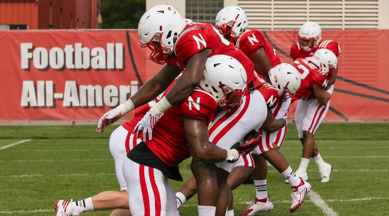 In this Aug. 9, 2016, photo, Nebraska's Tre Bryant, front left, and Nebraska's Tyrin Ferguson , front right, practice rugby-style tackling during NCAA college football team practice in Lincoln, Neb. Nebraska is the latest program to adopt rugby-style tack