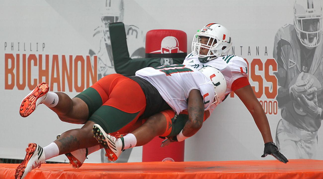 Miami's Gerald Willis, left, tackles Trent Harris, right, during NCAA college football practice, Thursday, Aug. 11, 2016 in Coral Gables, Fla. (Carl Juste/Miami Herald via AP)