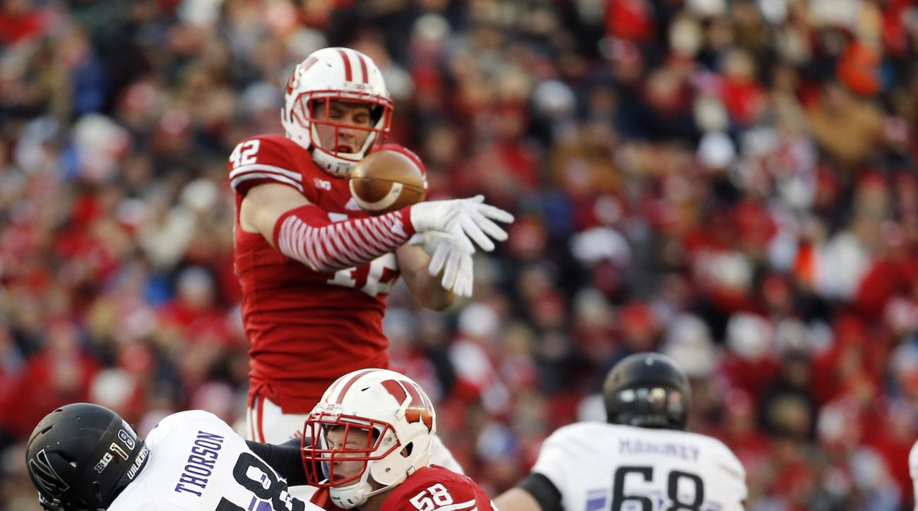 FILE - In this Nov. 21, 2015, file photo, Wisconsin's T.J. Watt (42), top, knocks down a pass thrown by Northwestern quarterback Clayton Thorson (18) during the first half of an NCAA college football game, in Madison, Wis. T.J. Watt, the younger brother o