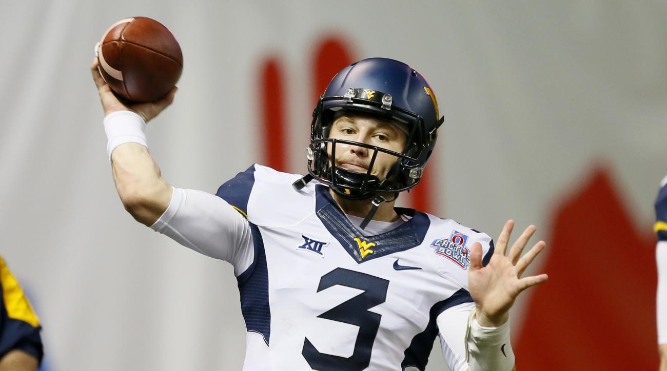 FILE - In this Jan. 2, 2016, file photo, West Virginia quarterback Skyler Howard (3) warms up for the Cactus Bowl NCAA College football game against Arizona State, in Phoenix. Howard is counting on a record 2015 bowl performance to help put to rest all th