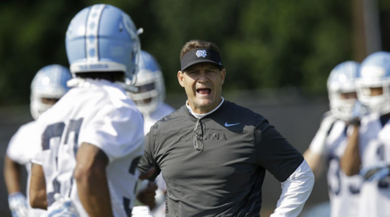 FILE - In this Monday, Aug. 3, 2015, file photo, North Carolina defensive coordinator Gene Chizik works with players during the team's first NCAA college football practice of the season in Chapel Hill, N.C. Chizik said the focus for this year's defense is
