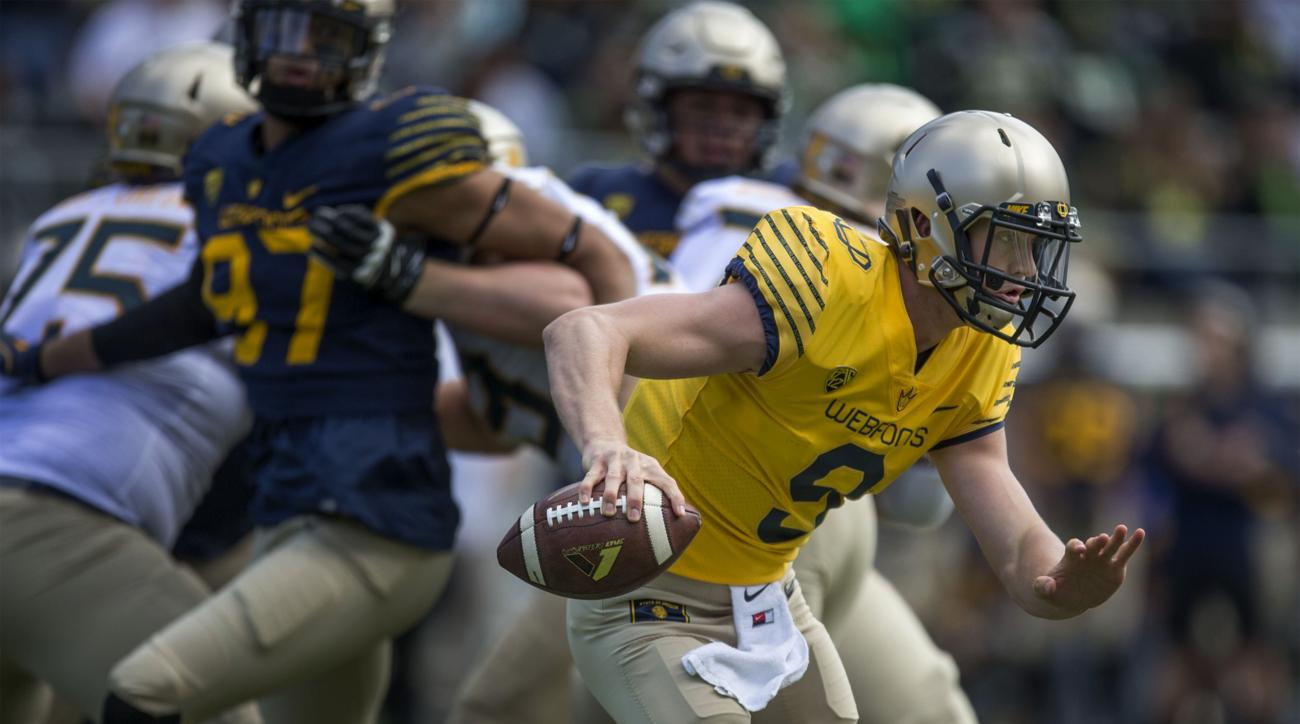 FILE - In this April 30, 2016, file photo, quarterback Dakota Prukop scrambles with the football during the Oregon Spring Game in Eugene, Ore. One year after Vernon Adams made a successful move from Eastern Washington to Oregon, the Ducks are seeing wheth