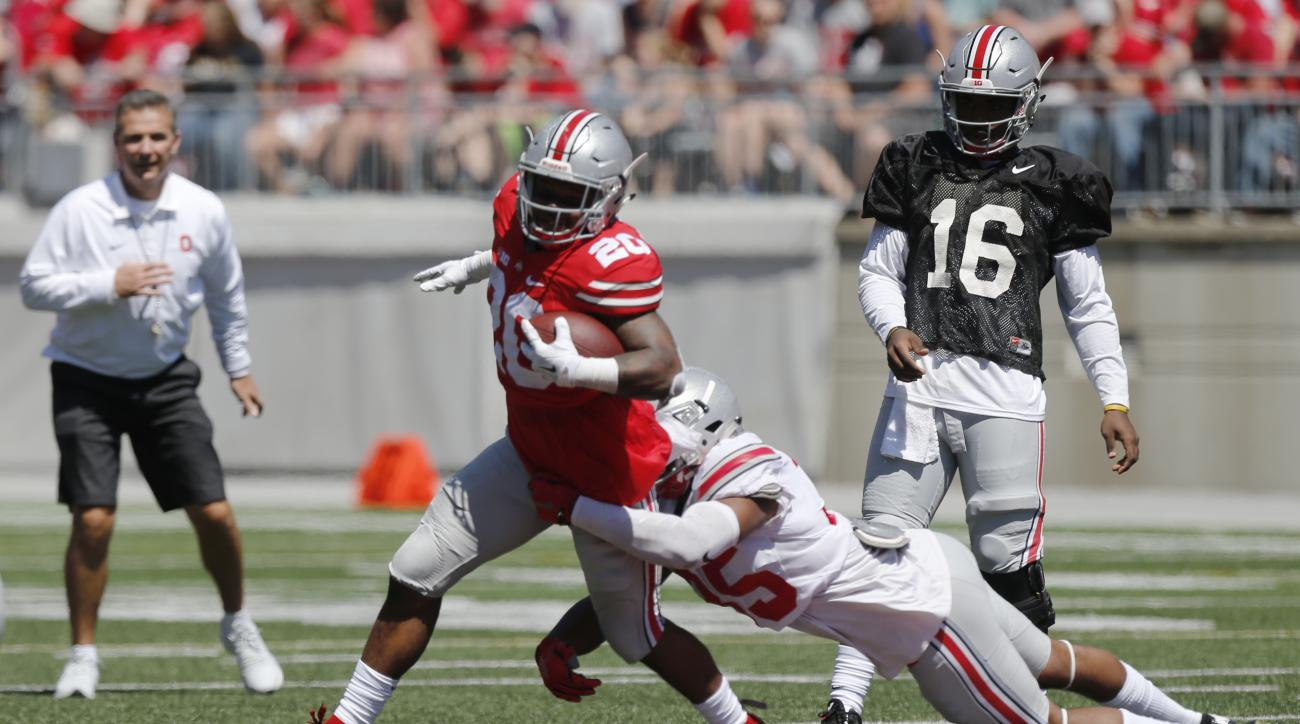 FILE - In this April 16, 2016, file photo, Ohio State running back Mike Weber, left, tries to avoid a tackle by linebacker Chris Worley during Ohio State's NCAA college football spring game, in Columbus, Ohio. At rear left is Ohio State coach Urban Meyer.
