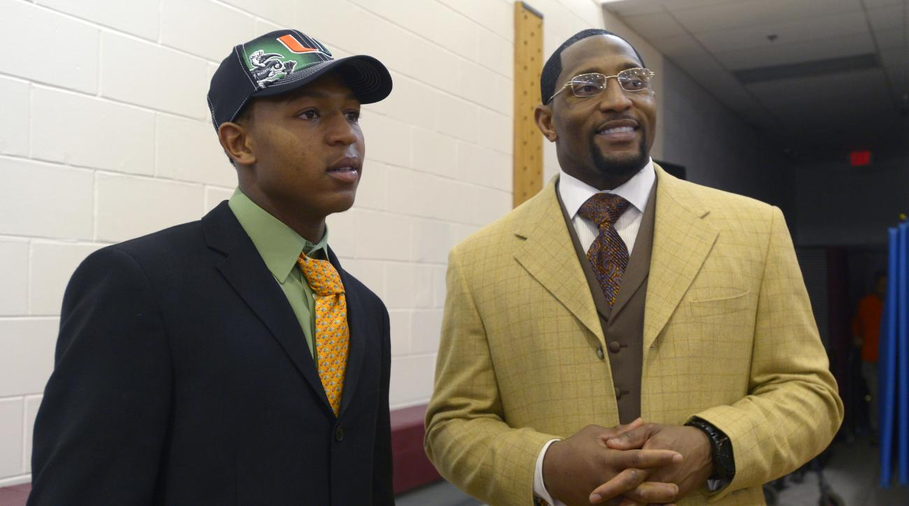 FILE - In this Feb. 6, 2013, file photo, Ray Anthony Lewis III, left, and his father, former Baltimore Ravens linebacker Ray Lewis Jr., chat after his national signing day ceremony in the Lake Mary Prep auditorium in Lake Mary, Fla. Lewis III, a Coastal C