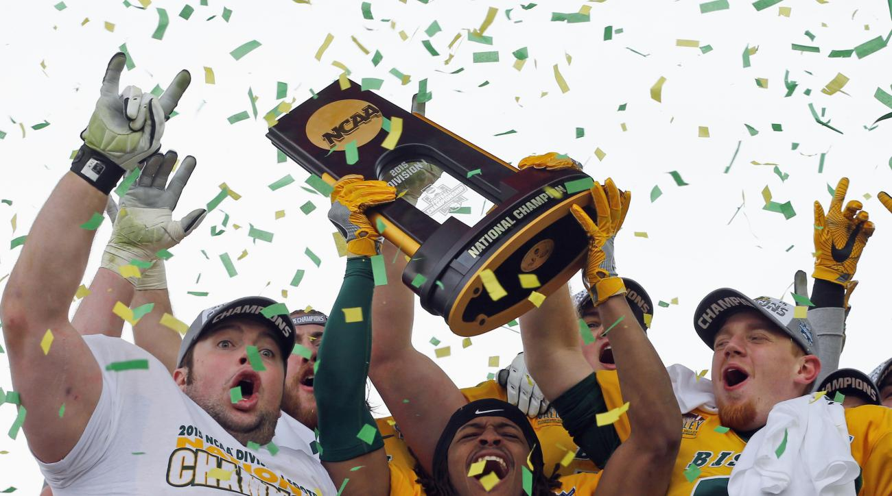 FILE - In this Jan. 9, 2016, file photo, North Dakota State players celebrate with the trophy after they defeated Jacksonville State 37-10 in the FCS championship NCAA college football game in Frisco, Texas. The Bison have won five straight FCS titles.  (