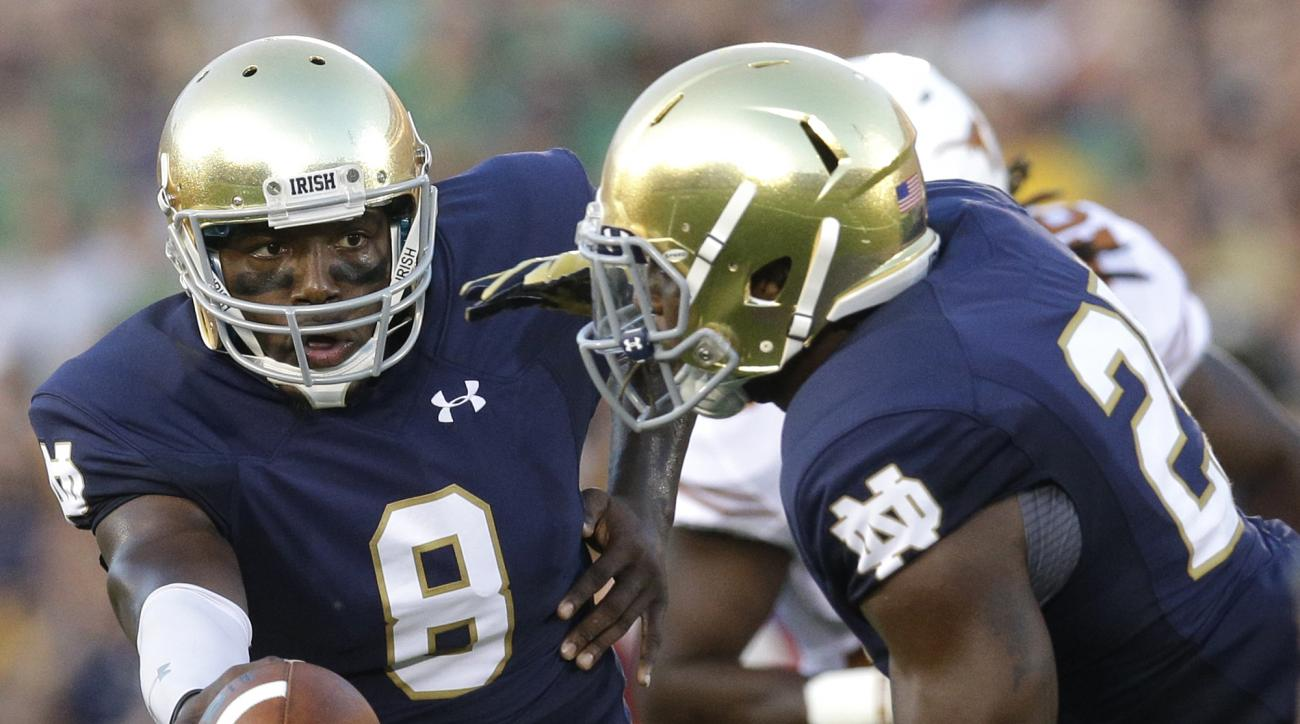 FILE - In this Saturday, Sept. 5, 2015 file photo, Notre Dame quarterback Malik Zaire, left, hands off to running back Tarean Folston during the first half of an NCAA college football game against Texas in South Bend, Ind. Zaire played brilliantly in a se