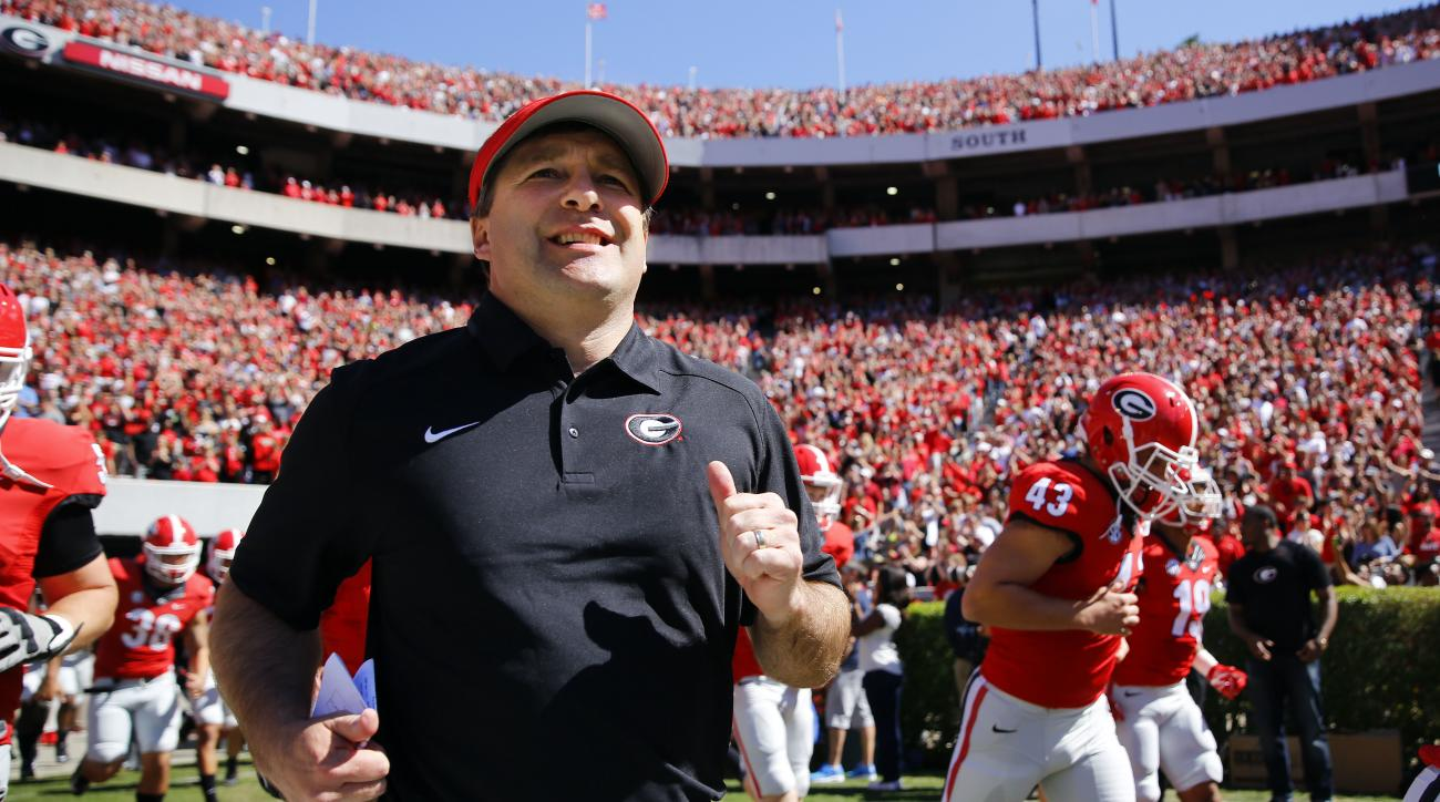 FILE - In this April 16, 2016 file photo, Georgia first-year head coach Kirby Smart runs into a packed Sandford Stadium with his players for the school's spring NCAA college football game in Athens, Ga. No. 18 Georgia begins the Kirby Smart era with a cha