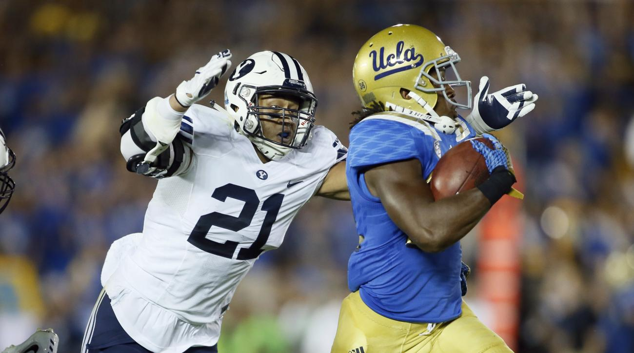 FILE - This Sept. 19, 2015, file photo, BYU linebacker Harvey Langi, left, dives to bring down UCLA running back Paul Perkins, right, on a long gain during the first half of an NCAA college football game, in Pasadena, Calif. Langi was the second-leading t