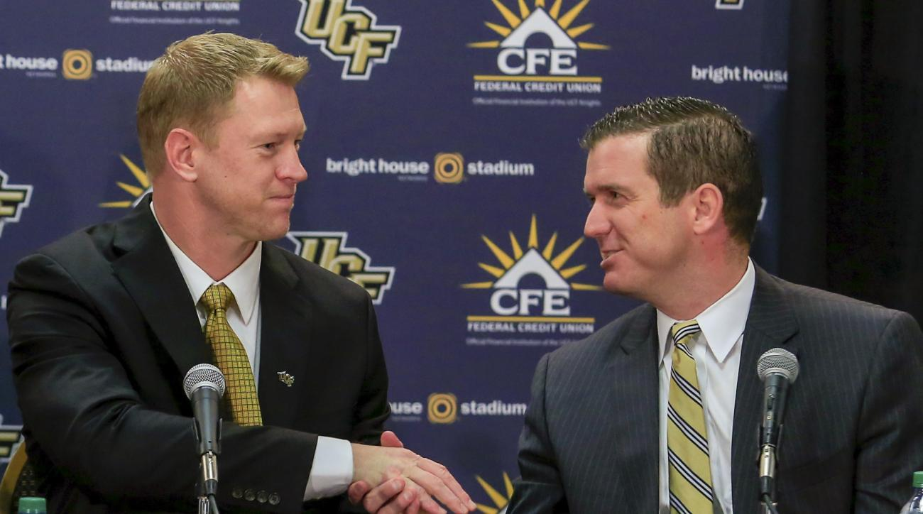 FILE - In this Dec. 2, 2015, file photo, Central Florida's new football coach, Scott Frost, left, shakes hands with athletic director Danny White at an introductory news conference in Orlando, Fla. With the Frost regimes official kickoff just days away, t