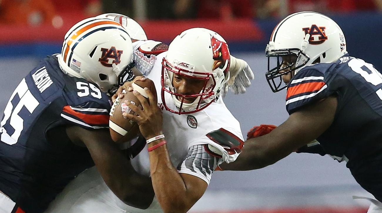 FILe - In this Sept. 5, 2015, file photo, Auburn defensive lineman Carl Lawson (55) tackles Louisville quarterback Reggie Bonnafon (7) during the first half of an NCAA college football game, in Atlanta. Auburn's defensive line is one of the best in the So