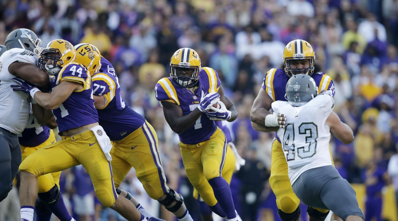 FILE - In this Oct. 3, 2015, file photo, LSU running back Leonard Fournette (7) carries past Eastern Michigan linebacker Anthony Zappone (43) in the first half of an NCAA college football game in Baton Rouge, La. Wisconsin and LSU are teams in transition