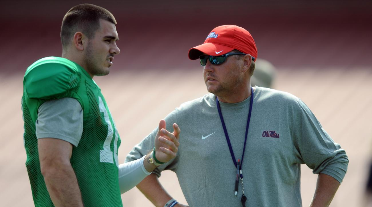 FILE - In this Aug. 10, 2015, file photo, Mississippi quarterback Chad Kelly, left, talks with head coach Hugh Freeze during NCAA college football practice in Oxford, Miss. Freeze made a surprise choice to protect the teams most valuable asset. Junior Rod