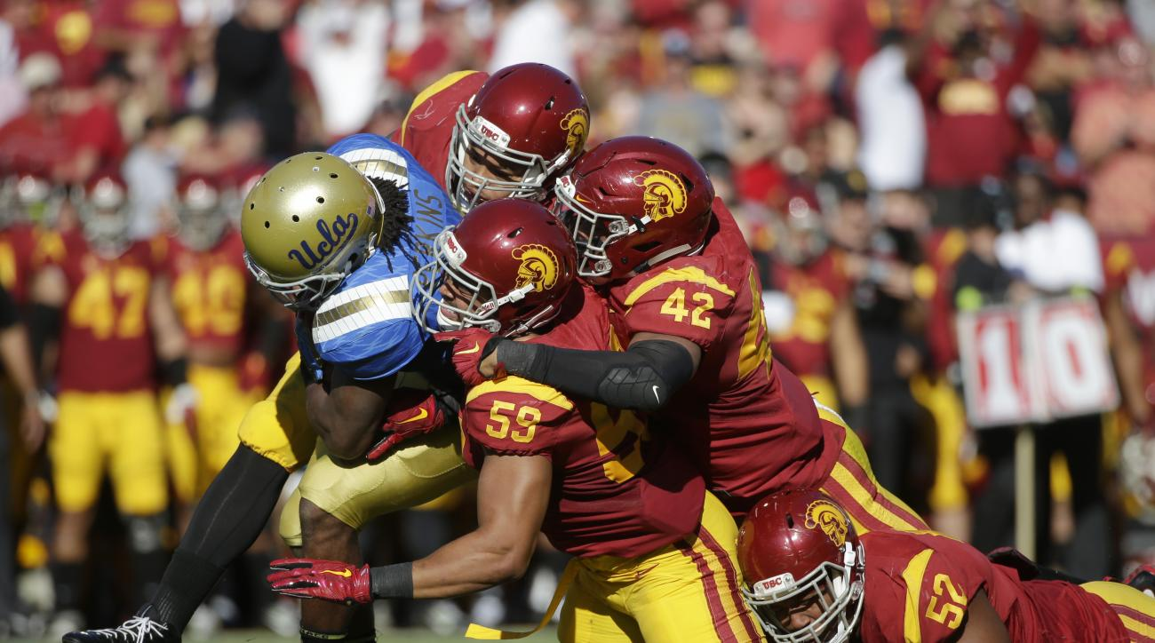 UCLA running back Paul Perkins, left, is brought down by Southern California's Don Hill (59), Uchenna Nwosu (42) and Delvon Simmons (52) during the first half of an NCAA college football game, Saturday, Nov. 28, 2015, in Los Angeles. (AP Photo/Jae C. Hong