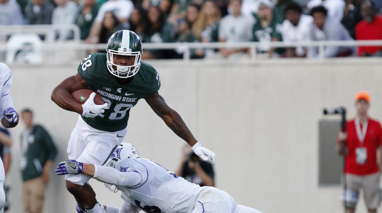 Michigan State's Madre London, left, carries as Furman's Carl Rider tries to make the tackle during the first quarter of an NCAA college football game, Friday, Sept. 2, 2016, in East Lansing, Mich. (AP Photo/Al Goldis)