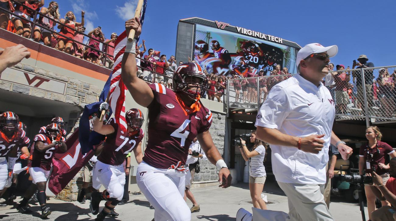 Virginia Tech head coach Justin Fuente, right, leads his team onto the field for the first half of an NCAA college football game agains Liberty in Blacksburg, Va., Saturday, Sept. 3, 2016. (AP Photo/Steve Helber)