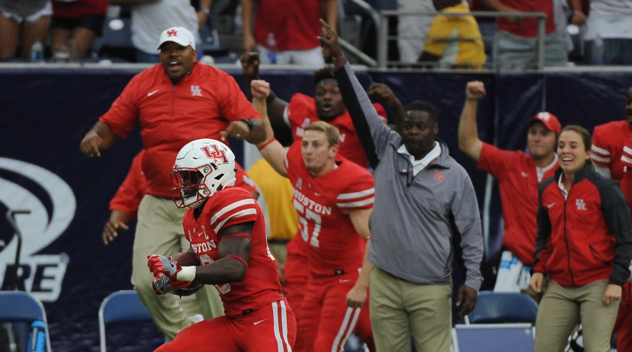 Houston cornerback Brandon Wilson (26) is cheered by the bench as he returns a missed field goal for a touchdown against Oklahoma in the second half of Houston's 33-23 victory in an NCAA college football game Saturday, Sept. 3, 2016, in Houston. (AP Photo