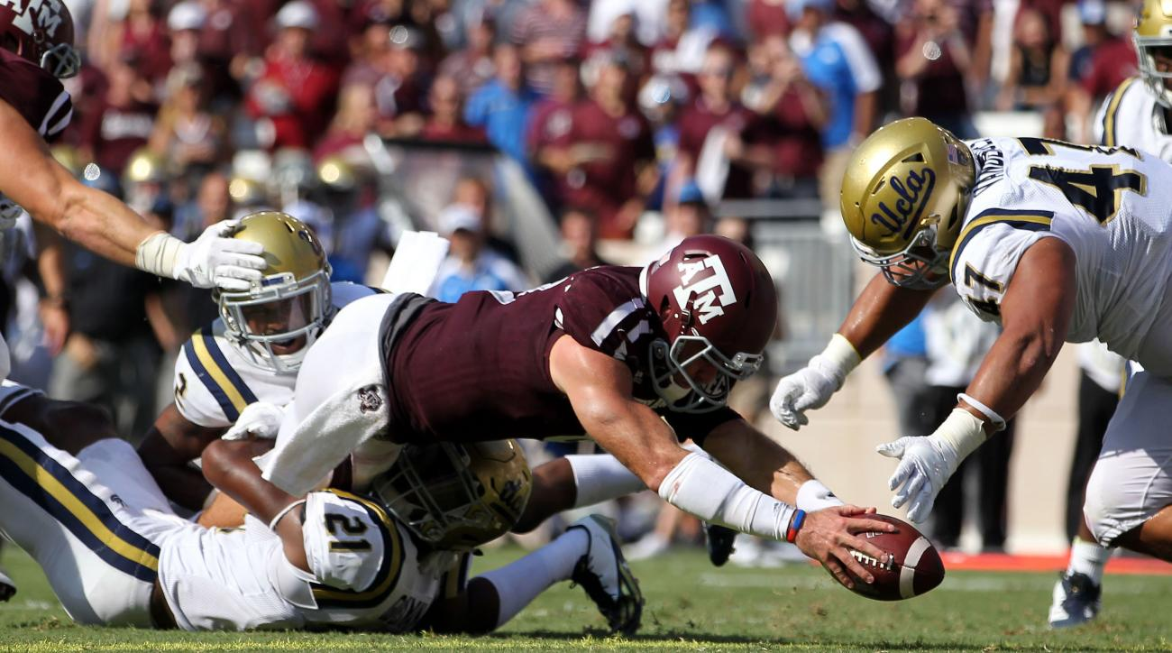 Texas A&M quarterback Trevor Knight (8) dives over the goal line for a touchdown as UCLA defensive back Tahaan Goodman (21) attempts to tackle him during the third quarter of an NCAA college football game Saturday, Sept. 3, 2016, in College Station, Texas
