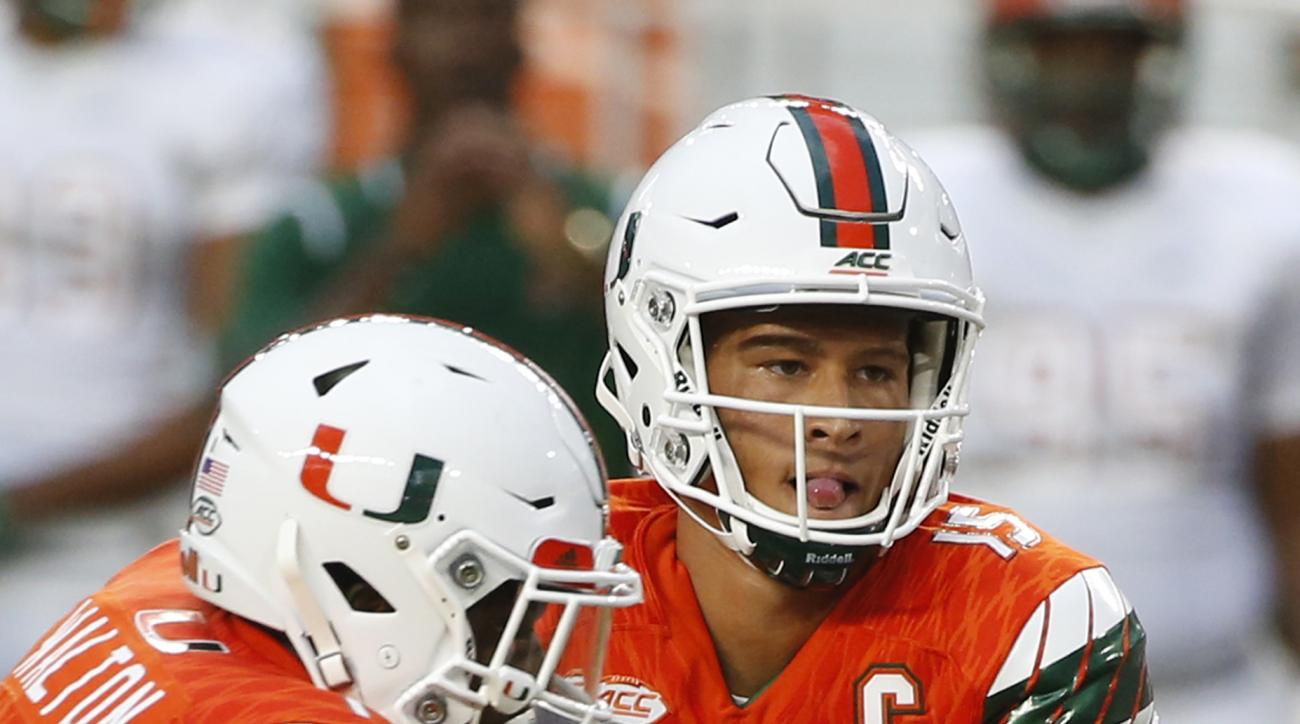 Miami quarterback Brad Kaaya (15) hands off to running back Mark Walton (1) during the first half of an NCAA college football game against Florida A&M, Saturday, Sept. 3, 2016 in Miami Gardens, Fla. (AP Photo/Wilfredo Lee)
