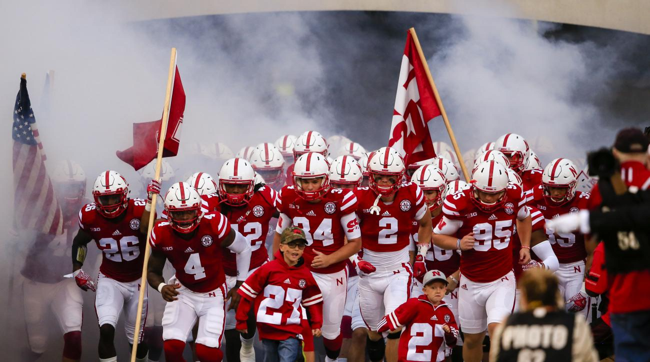 Nephews of deceased Nebraska punter Sam Foltz, Lane Foltz, left, and Max Foltz, right, join the team as they run onto the field, before an NCAA college football game against Fresno State in Lincoln, Neb., Saturday, Sept. 3, 2016. (AP Photo/Nati Harnik)