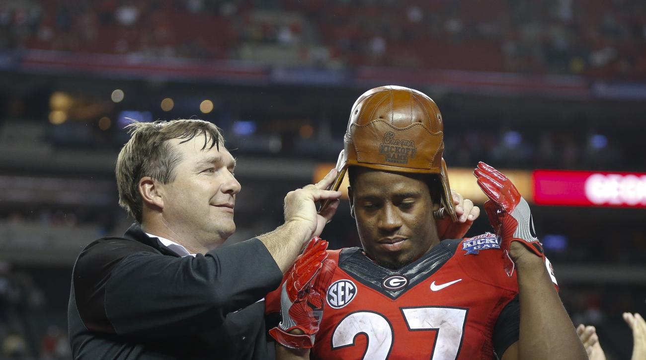 "Georgia head coach Kirby Smart puts the ""Old Leather Helmet"" on running back Nick Chubb's head after an NCAA college football game against North Carolina in Atlanta, Saturday, Sept. 3, 2016. Georgia won 33-24. The helmet is part of a trophy awarded to the"