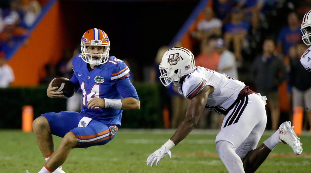 Florida quarterback Luke Del Rio (14) scrabbles for a short gain before he is stopped by Massachusetts linebacker Da'Sean Downey, right, during the second half of an NCAA college football game, Saturday, Sept. 3, 2016, in Gainesville, Fla. (AP Photo/John