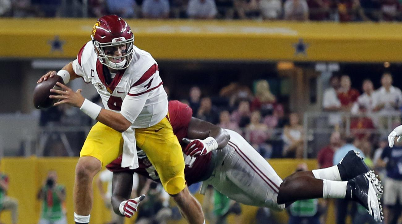 Southern California quarterback Max Browne scrambles away from Alabama defensive lineman Dalvin Tomlinson during the second half of an NCAA college football game Saturday, Sept. 3, 2016, in Arlington, Texas. (AP Photo/Tony Gutierrez)