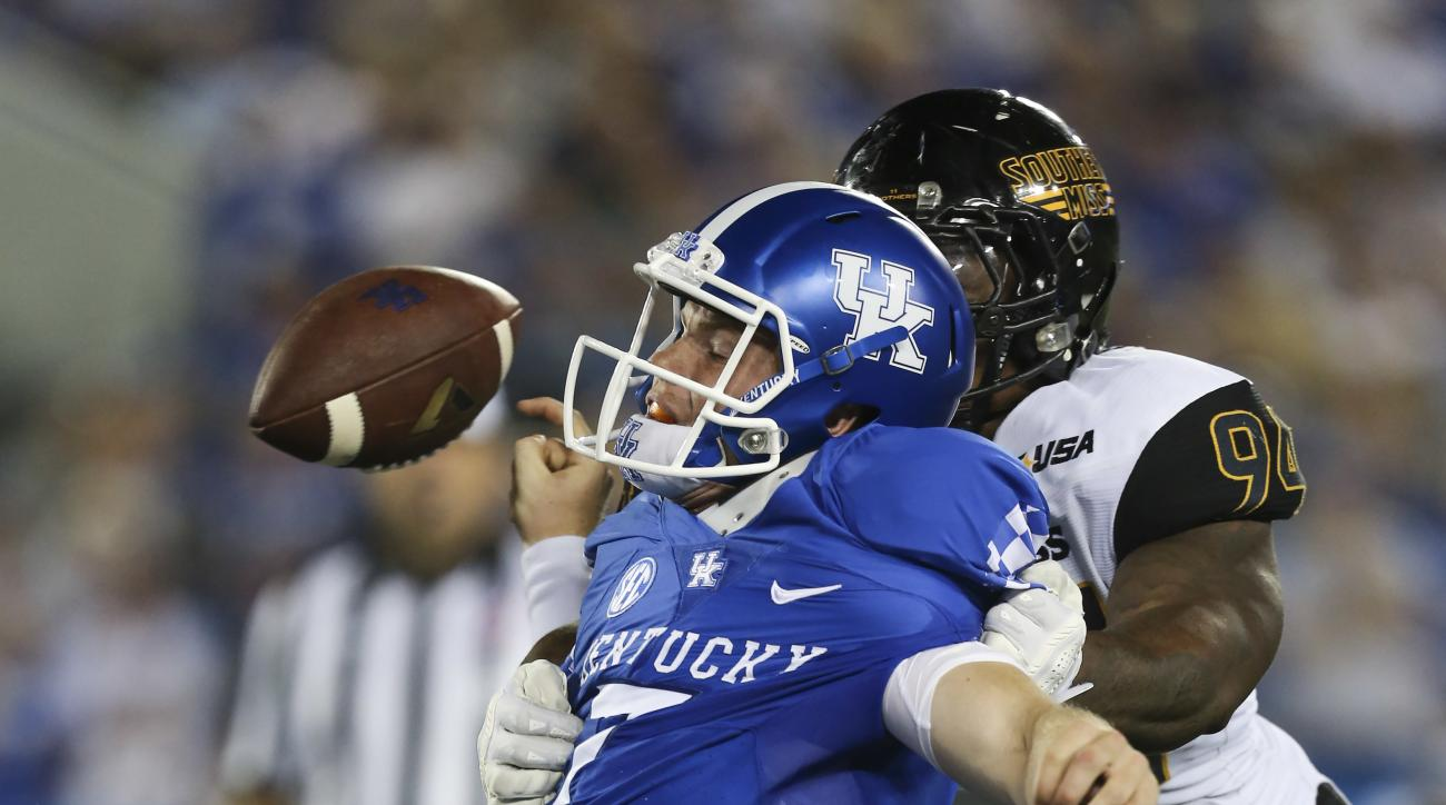Kentucky quarterback Drew Barker has the ball stripped by Southern Mississippi defensive lineman Dylan Bradley, resulting in a turnover in the second half of an NCAA college football game Saturday, Sept. 3, 2016, in Lexington, Ky. Southern Mississippi won