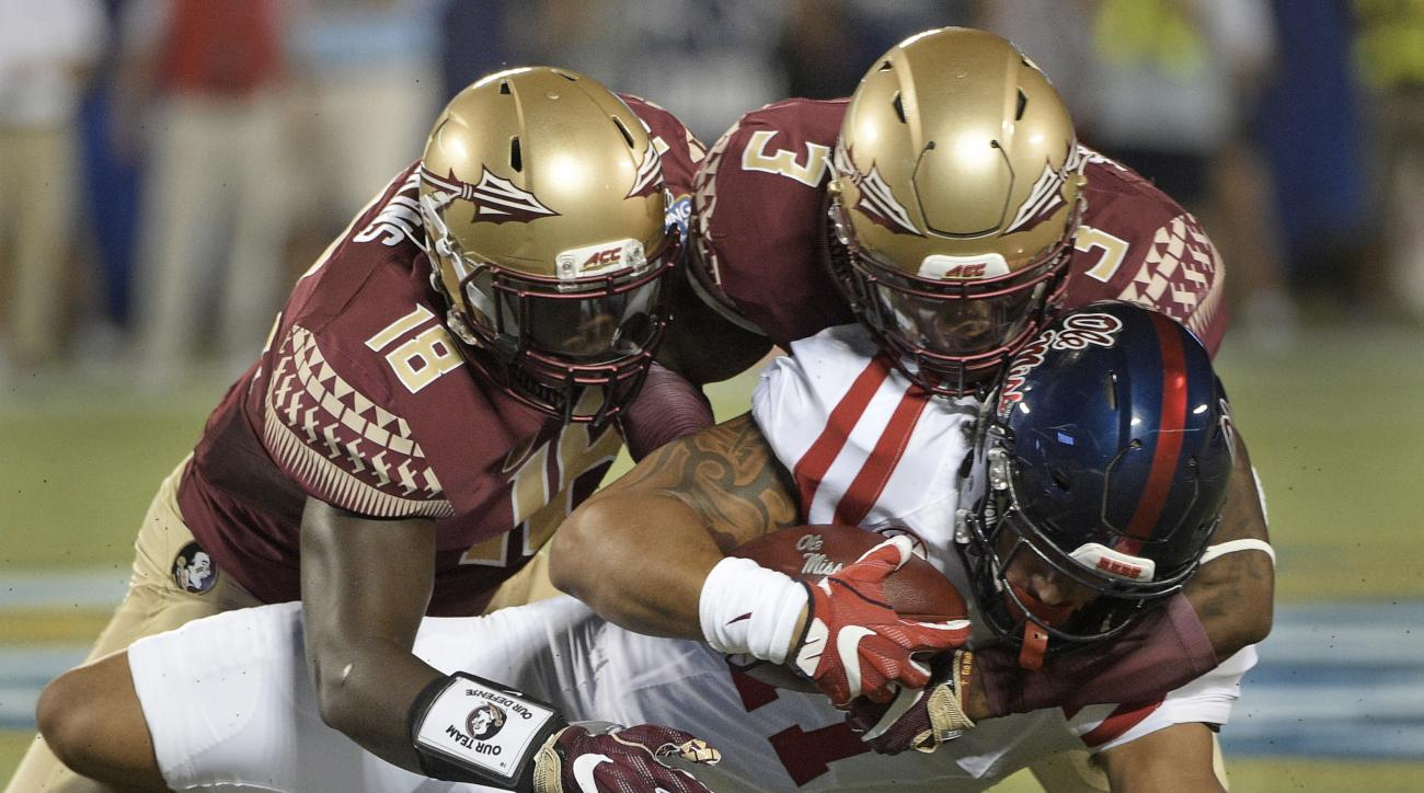 Mississippi tight end Evan Engram, center, is brought down, after a reception, by Florida State linebacker Ro'Derrick Hoskins (18) and defensive back Derwin James (3) during the first half of an NCAA college football game, Monday, Sept. 5, 2016, in Orland