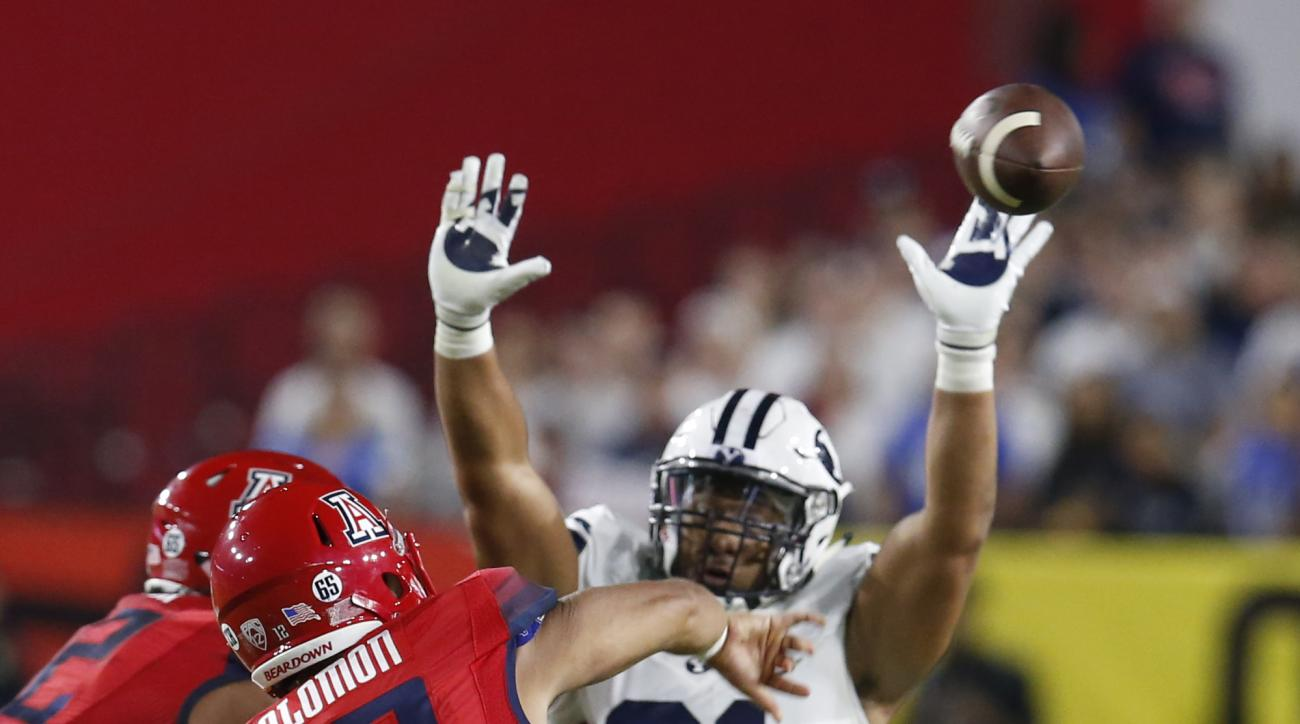 FILE - In this Saturday, Sept. 3, 2016, file photo, BYU linebacker Harvey Langi (21) pressures Arizona quarterback Anu Solomon (12) during an NCAA college football game in Phoenix. BYU and Utah may have as much crossover within the two programs as any two
