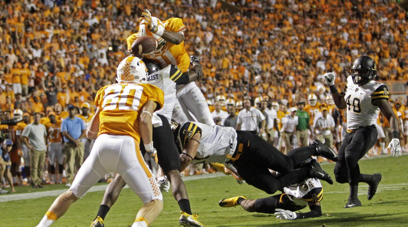 FILE -- In this Sept. 1, 2016 file photo, Tennessee quarterback Joshua Dobbs (11) leaps for the end zone as he's hit by Appalachian State linebacker Kennan Gilchrist (6), defensive lineman Caleb Fuller (51) and defensive back Desmond Franklin (34) during