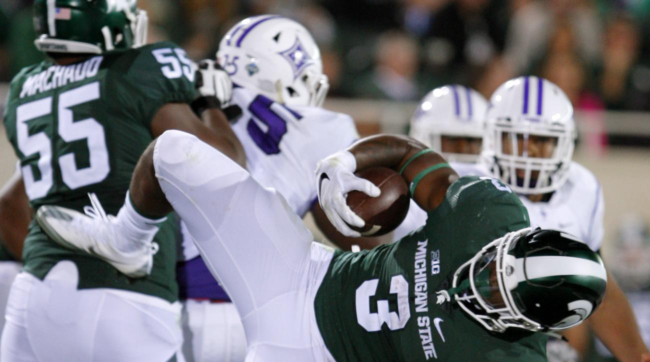FILE - In this Friday, Sept. 2, 2016, file phot,o Michigan State's LJ Scott (3) dives for a first down against Furman during the third quarter of an NCAA college football game in East Lansing, Mich. Michigan State had a lot to work on after an uninspiring