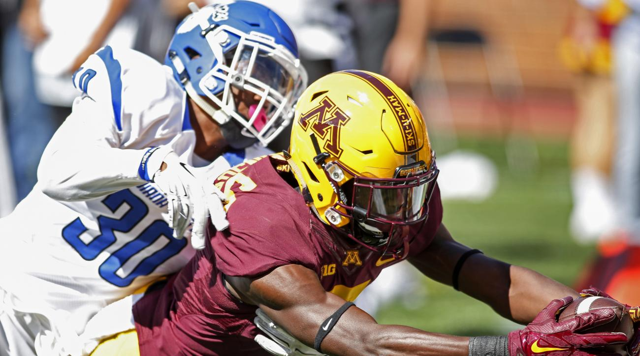 Minnesota wide receiver Tyler Johnson reaches over the goal line for a touchdown beyond the defense of Indiana State defensive back Kevin Beacham in the second quarter of an NCAA college football game Saturday, Sept. 10, 2016, in Minneapolis. (AP Photo/Br