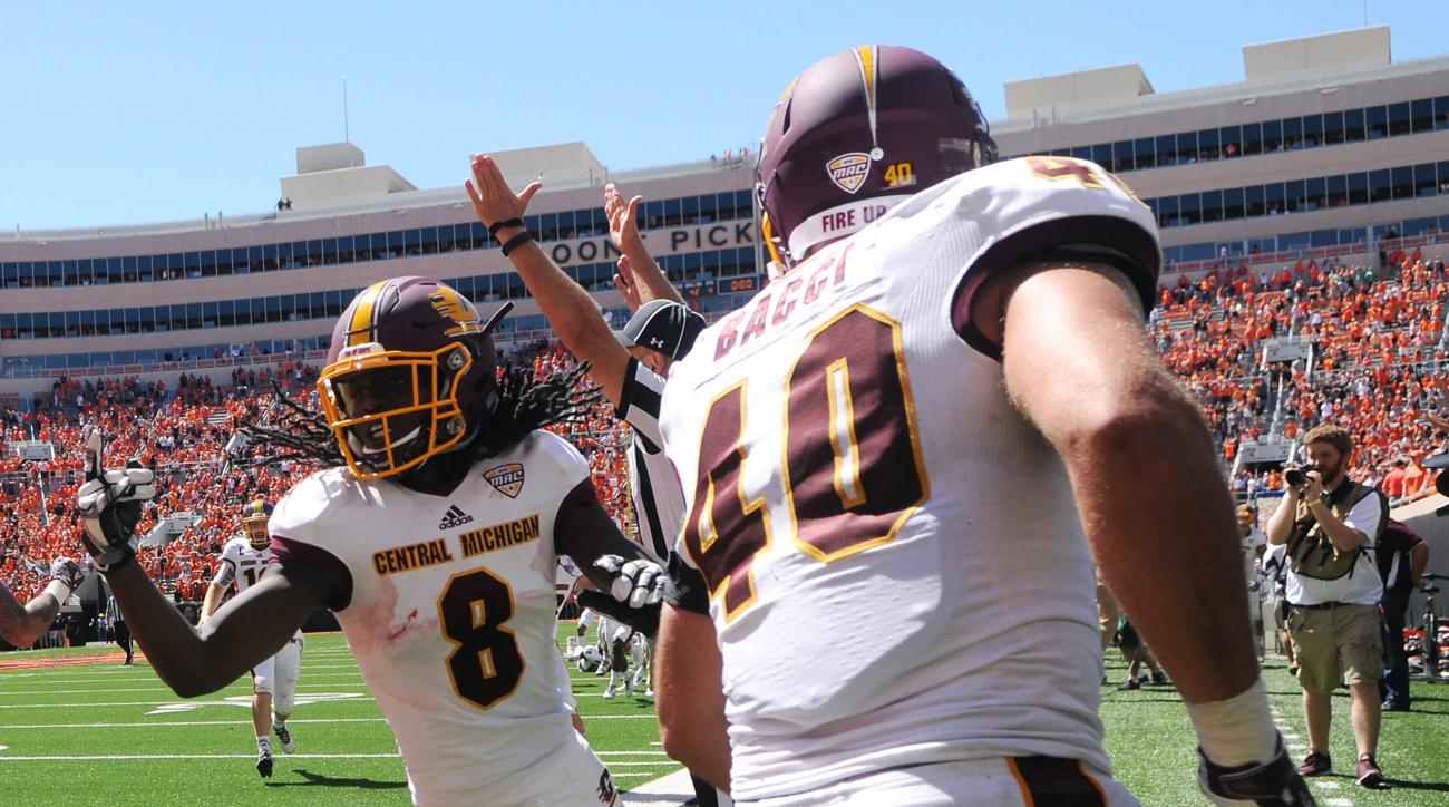A referee signals a touchdown as Central Michigan wide receiver Corey Willis (8) celebrates with his teammate running back Joe Bacci (40) after scoring the winning touchdown in the final seconds of an NCAA college football game between against Oklahoma St
