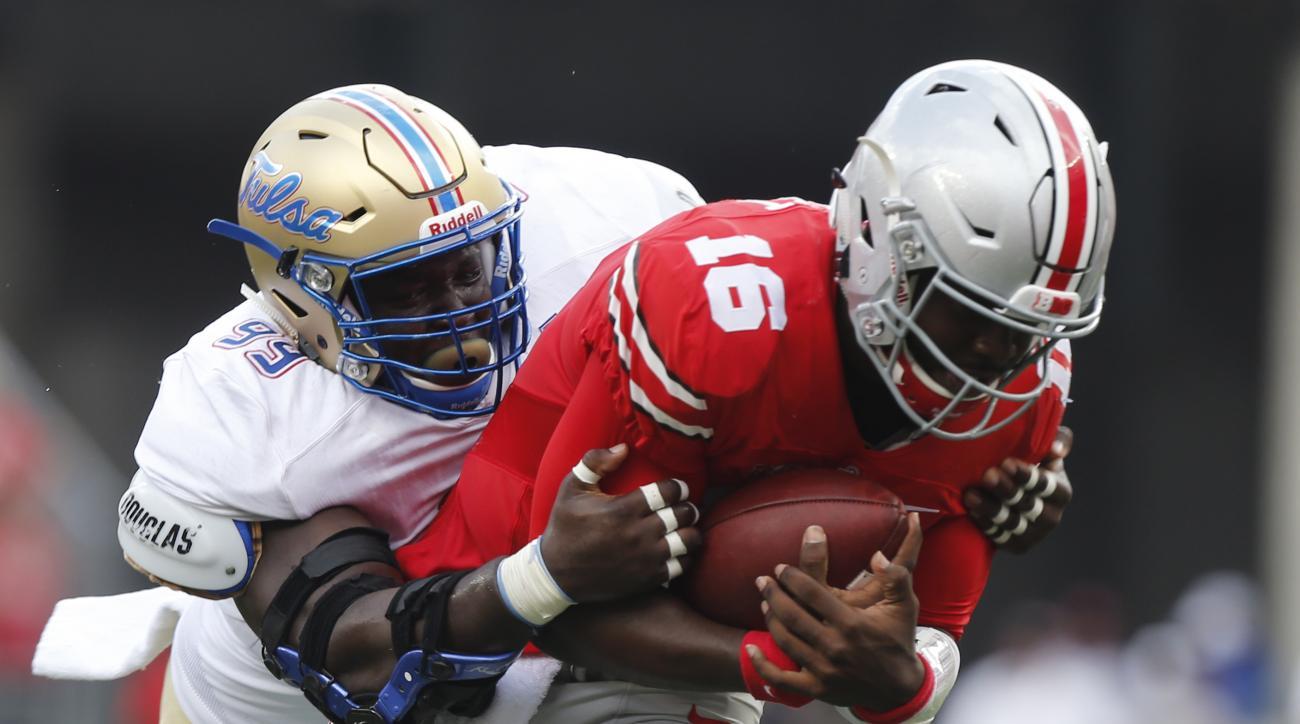Tulsa defensive lineman Jerry Uwaezuoke, left, tackles Ohio State quarterback J.T. Barrett during the first half of an NCAA college football game, Saturday, Sept. 10, 2016, in Columbus, Ohio. (AP Photo/Jay LaPrete)