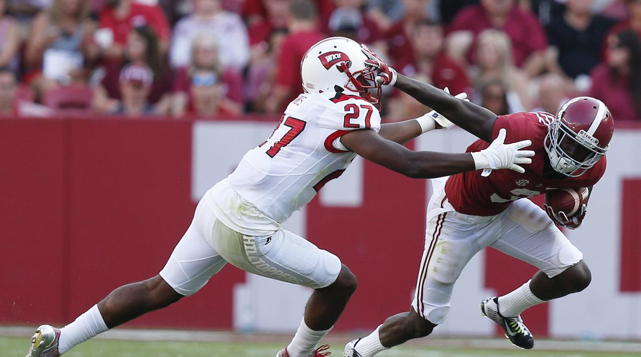 Alabama wide receiver Calvin Ridley avoids the tackle with a stiff arm against Western Kentucky defensive back Martavius Mims during the second half of an NCAA college football game, Saturday, Sept. 10, 2016, in Tuscaloosa, Ala. Alabama won 38-10. (AP Pho
