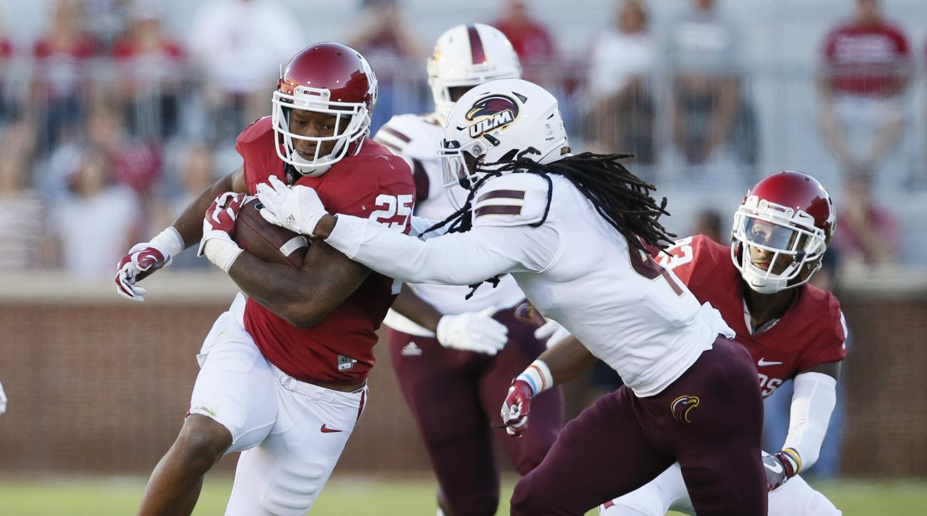 Louisiana Monroe safety Tre' Hunter, front right, moves in to tackle Oklahoma running back Joe Mixon (25) in the first quarter of an NCAA college football game in Norman, Okla., Saturday, Sept. 10, 2016. (AP Photo/Sue Ogrocki)