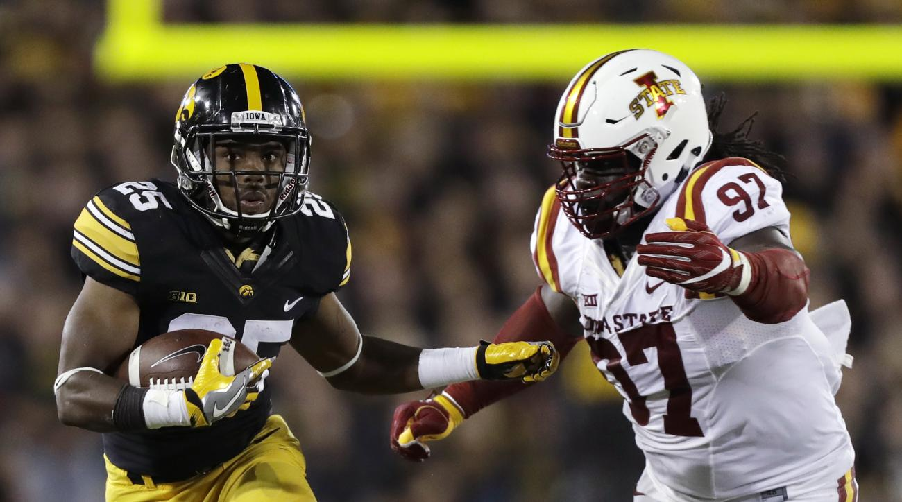 Iowa running back Akrum Wadley runs from Iowa State defensive lineman Demond Tucker, right, during the first half of an NCAA college football game, Saturday, Sept. 10, 2016, in Iowa City, Iowa. (AP Photo/Charlie Neibergall)
