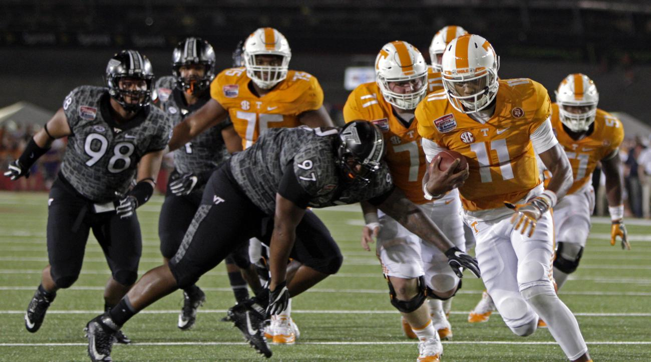 Tennessee quarterback Joshua Dobbs (11) for a touchdown while being chased by Virginia Tech defensive tackle Tim Settle (97) during an NCAA college football game at Bristol Motor Speedway on Saturday, Sept. 10, 2016, in Bristol, Tenn. (AP Photo/Wade Payne