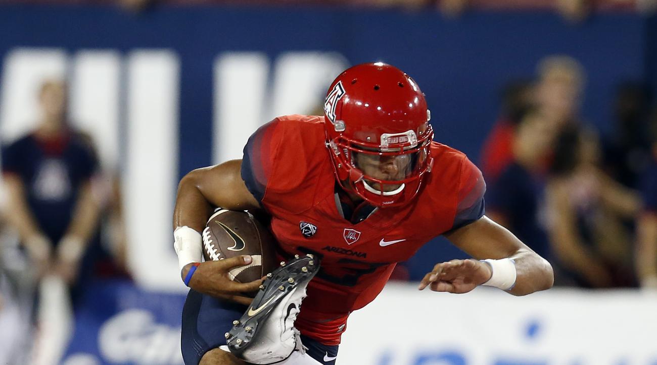 Arizona quarterback Brandon Dawkins (13) runs over Grambling State linebacker Christian Bailey (50) during the first half of an NCAA college football game, Saturday, Sept. 10, 2016, in Tucson, Ariz. (AP Photo/Rick Scuteri)