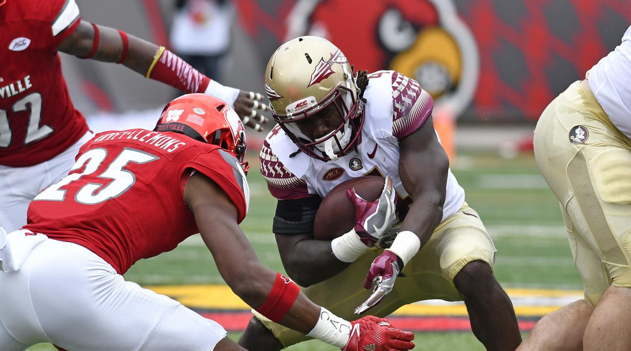 Florida State's Dalvin Cook, center, is hit by Louisville's Josh Harvey-Clemons (25) during the first quarter of an NCAA college football game, Saturday, Sep. 17, 2016 in Louisville Ky. (AP Photo/Timothy D. Easley)
