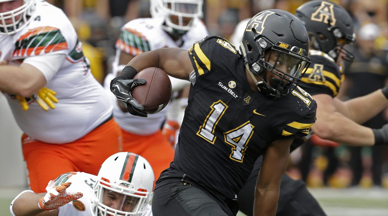 Appalachian State's Marcus Cox (14) runs past Miami's Trent Harris (33) during the first half of an NCAA college football game in Boone, N.C., Saturday, Sept. 17, 2016. (AP Photo/Chuck Burton)