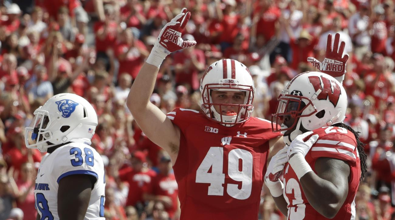 Wisconsin's Dare Ogunbowale is congratulated by teammate Kyle Penniston (49) after his touchdown run during the second half of an NCAA college football game against Georgia State Saturday, Sept. 17, 2016, in Madison, Wis. Wisconsin won 23-17. (AP Photo/Mo