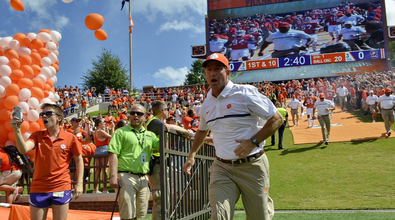 Clemson head coach Dabo Swinney runs down the hill before the start of an NCAA college football game against South Carolina State Saturday, Sept. 17, 2016, in Clemson, S.C. (AP Photo/Richard Shiro)